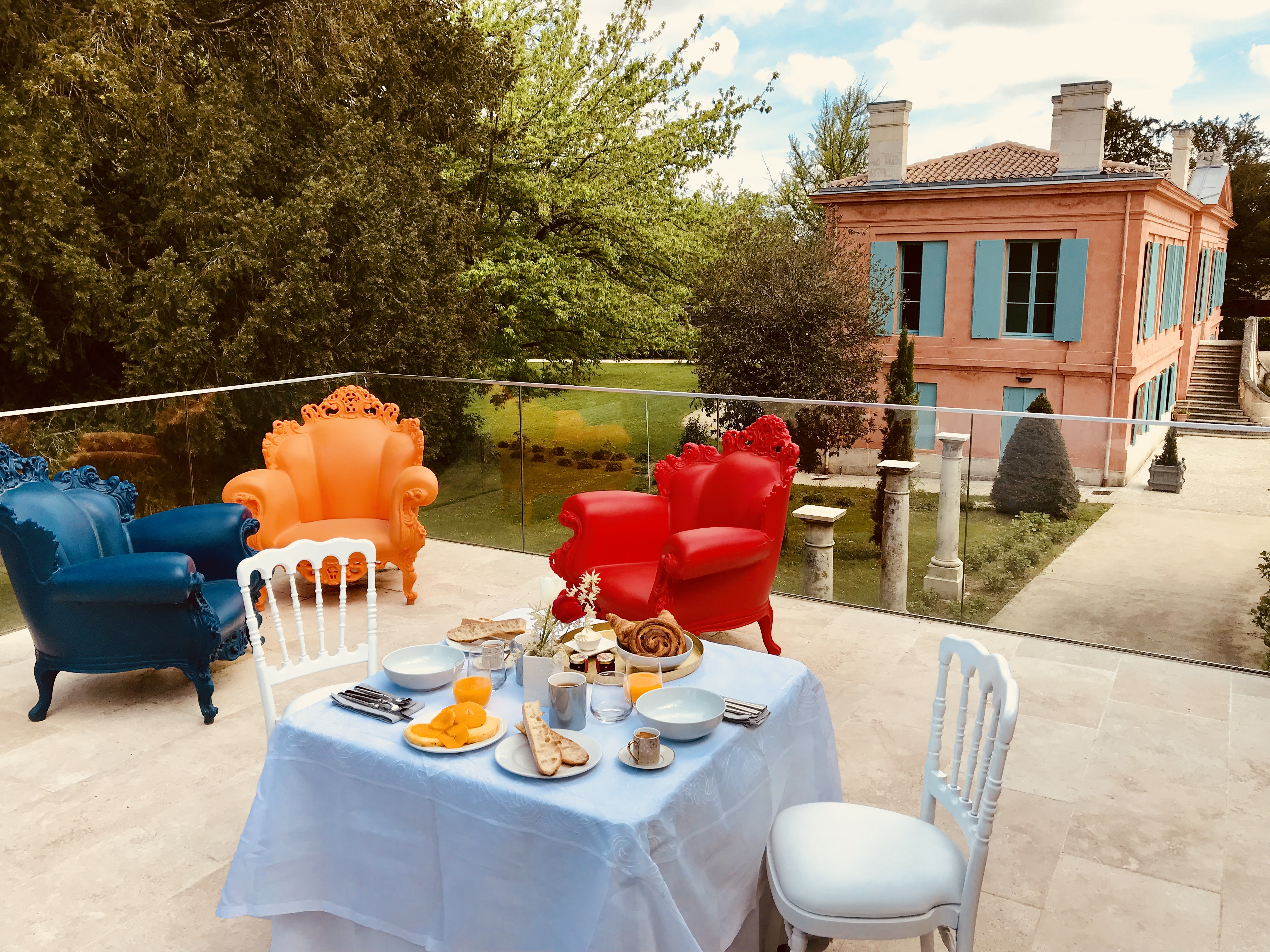 photo de la terrasse des chambres d'hôtes devant le château Pont St Martin, mise en scène avec une table dressée et fauteuils colorés