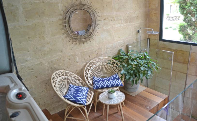 photo détail de la douche du jacuzzi, fauteuil et miroir en osier avec coussins bleus et blancs, chambres d'hôtes château Pont Saint-Martin, Pessac Léognan, Bordeaux