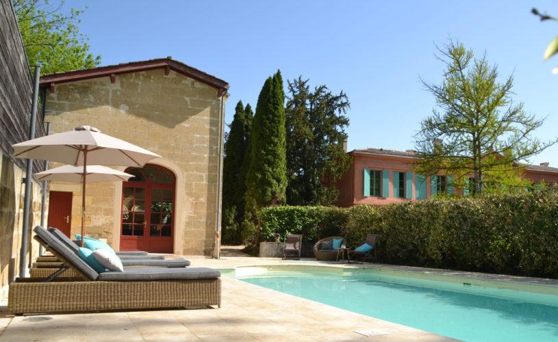 photo de l'extérieur du château avec vue sur la piscine, mise en scène avec fauteuils de piscine
