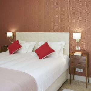 photo détail de la chambre Ausone, lit avec coussins rouge, tête de lit blanche et tapisserie ocre-rouge, chambres d'hôtes château Pont Saint-Martin, Pessac Léognan, Bordeaux, dégustation de vin, tout confort